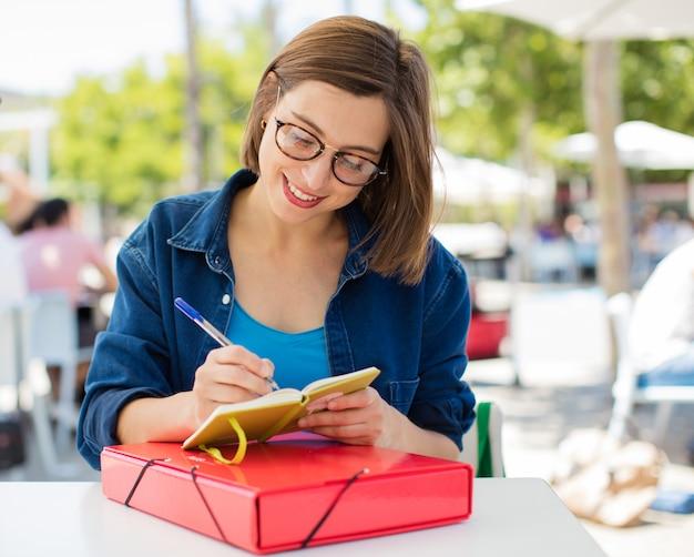 Jeune femme écrivant à l'université