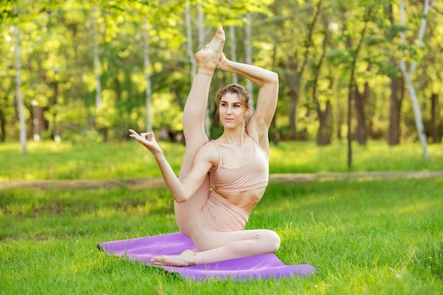 Jeune femme effectue du yoga dans le parc. séance de méditation corps équilibre
