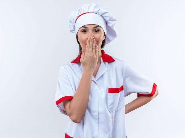 Jeune femme effrayée cuisinier portant l'uniforme du chef bouche couverte avec la main isolée sur mur blanc