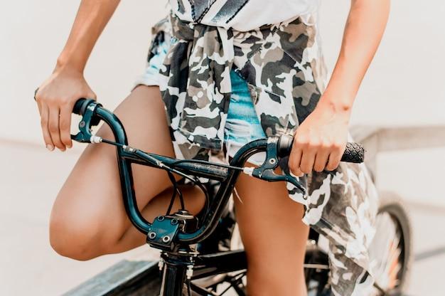 Jeune femme élancée assise sur le vélo, tenant le guidon avec les mains.