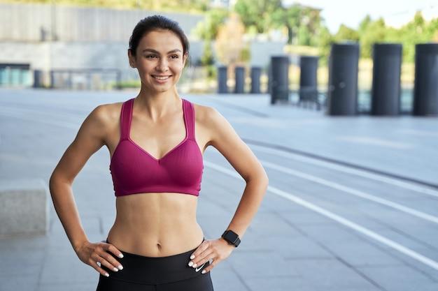 Jeune femme élancée en haut de sport posant dans la rue et souriante. notion de sport. espace de copie