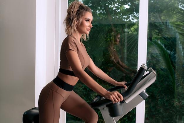 Une jeune femme élancée s'entraîne sur un vélo d'exercice dans une salle de sport en vêtements de sport à la mode. vue de côté