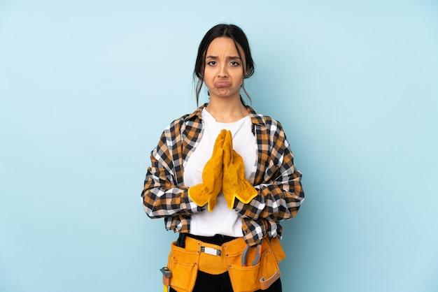 Jeune femme électricien sur mur bleu garde la paume ensemble. la personne demande quelque chose