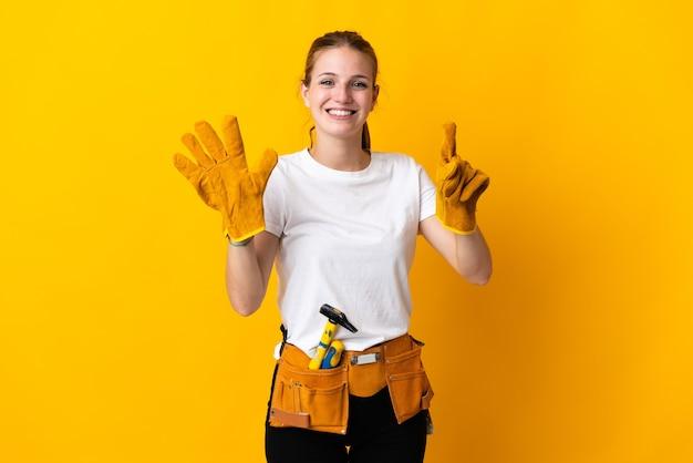 Jeune femme électricienne isolée sur fond jaune comptant six avec les doigts