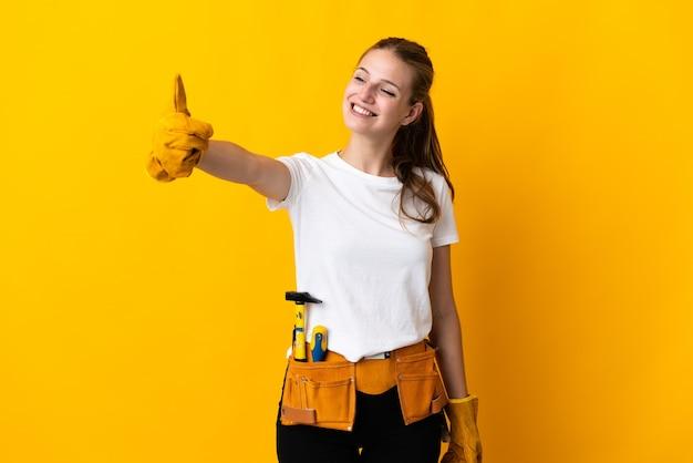 Jeune femme électricienne isolée sur fond jaune donnant un geste de pouce en l'air