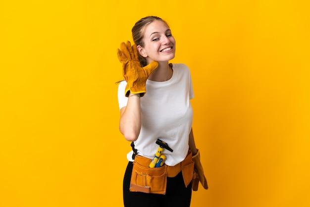 Jeune femme électricienne isolée sur fond jaune, écouter quelque chose en mettant la main sur l'oreille