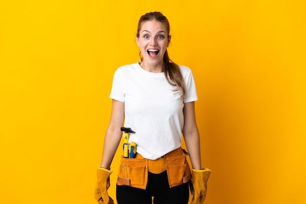 Jeune femme électricienne isolée sur fond jaune avec une expression faciale surprise