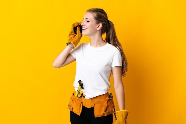 Jeune femme électricienne isolée sur fond jaune en gardant une conversation avec le téléphone mobile