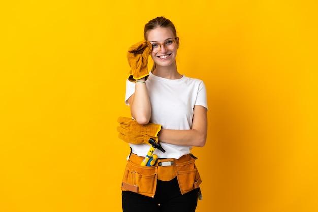 Jeune femme électricienne isolée sur fond jaune avec des lunettes et heureux