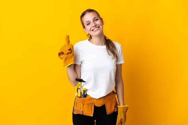Jeune femme électricienne isolée sur fond jaune montrant et en soulevant un doigt en signe du meilleur