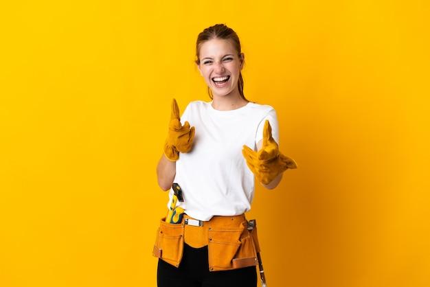 Jeune femme électricienne isolée sur fond jaune pointant vers l'avant et souriant