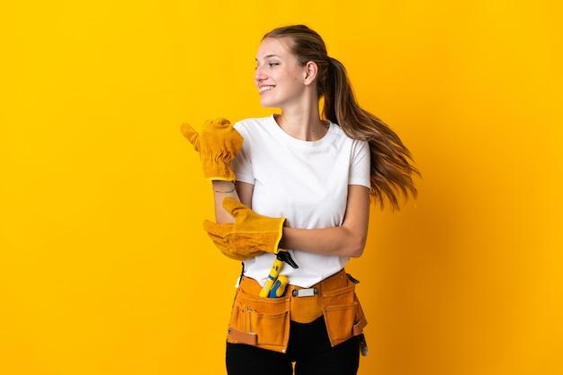 Jeune femme électricienne isolée sur fond jaune pointant vers le côté pour présenter un produit