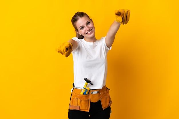 Jeune femme électricienne isolée sur fond jaune pointe le doigt sur vous en souriant