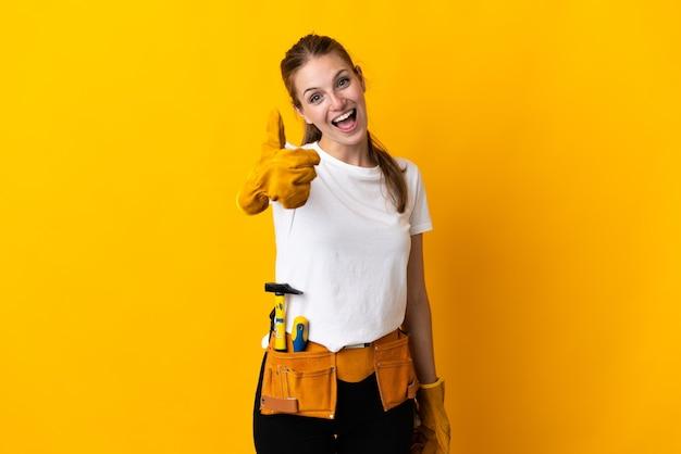 Jeune femme électricienne isolée sur fond jaune avec les pouces vers le haut parce que quelque chose de bien s'est passé