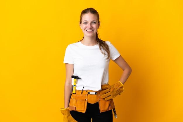 Jeune femme électricienne isolée sur fond jaune en riant