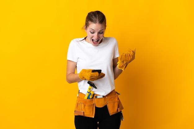 Jeune femme électricienne isolée sur fond jaune surpris et envoyant un message