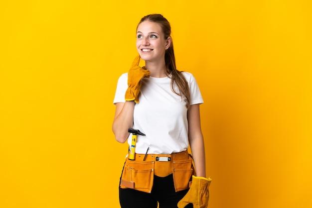 Jeune femme électricienne isolée sur jaune pensant une idée tout en levant