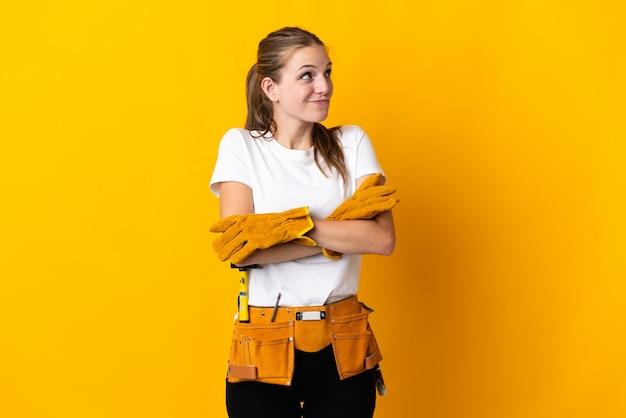 Jeune femme électricienne isolée sur mur jaune faisant des doutes tout en soulevant les épaules
