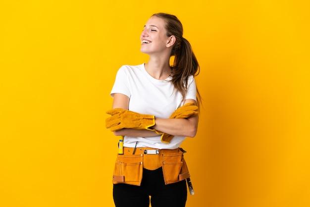 Jeune femme électricienne isolée sur mur jaune heureux et souriant