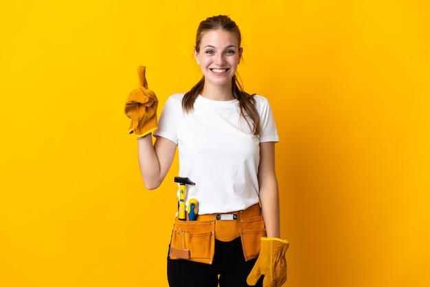 Jeune femme électricienne isolée sur mur jaune pointant avec l'index une excellente idée