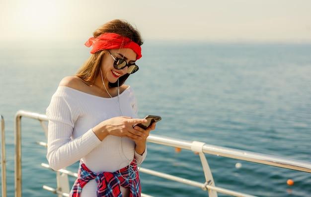 Une jeune femme élégamment vêtue écoute de la musique dans des écouteurs et utilise un smartphone sur la plage sur fond de mer
