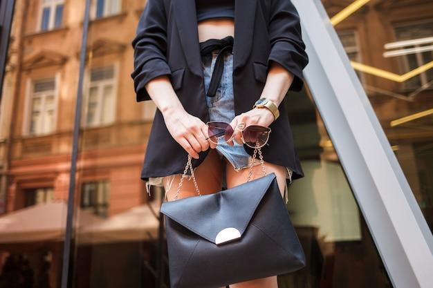 Jeune femme élégamment vêtue tient un sac à main et des lunettes dans ses mains.