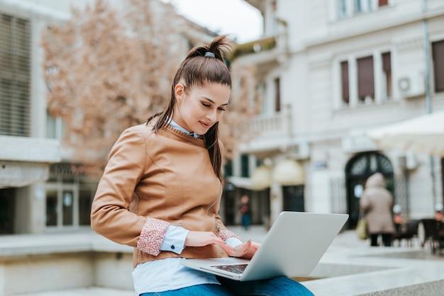 Jeune femme élégante à l'aide d'un ordinateur portable dans une rue.