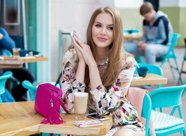 Jeune femme élégante assise au café