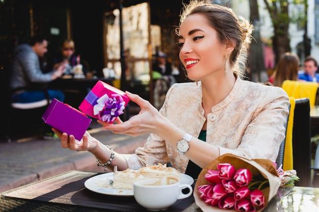 Jeune femme élégante assise dans un café, tenant la boîte présente, souriant