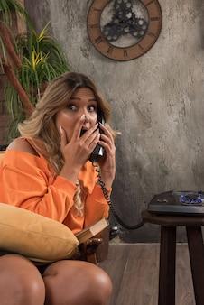Jeune femme élégante assise dans un fauteuil parlant avec téléphone surpris.