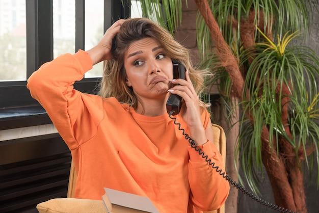 Jeune femme élégante assise dans un fauteuil, parler avec téléphone tenant ses cheveux.
