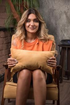 Jeune femme élégante assise dans un fauteuil tenant un oreiller dans la chambre.