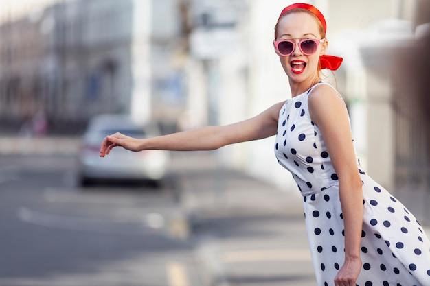Jeune femme élégante attrape un taxi dans la rue.