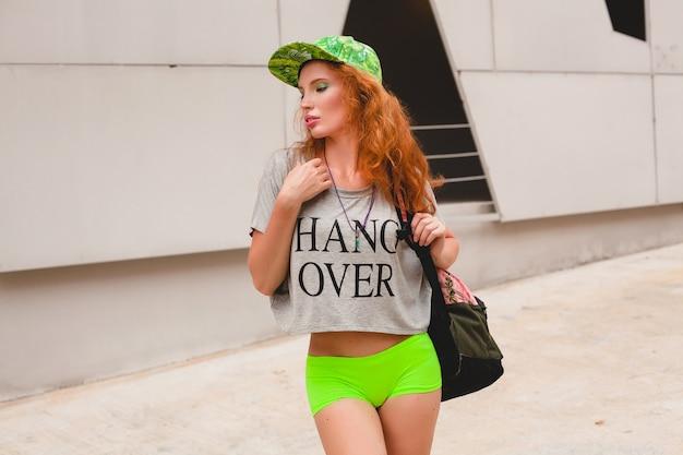 Jeune femme élégante au gingembre hipster, marchant dans la rue, casquette verte, t-shirt surdimensionné gris, s'amuser, vêtements à la mode, tenue de mode, style adolescent urbain, sac à dos, voyageur