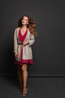 Jeune femme élégante aux cheveux bouclés et au maquillage parfait portant une robe rose et un trench-coat à la mode posant sur fond gris