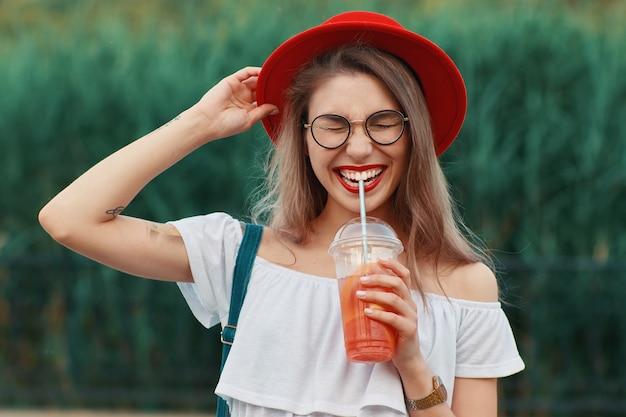 Une jeune femme élégante ayant une boisson rafraîchissante en marchant