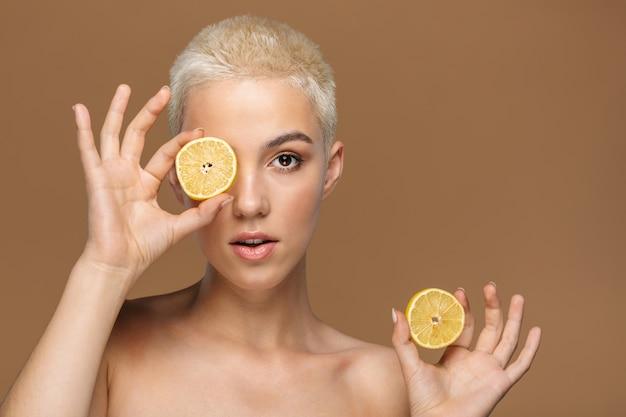 Une jeune femme élégante blonde sérieuse avec une coupe de cheveux courte posant isolée sur un mur beige foncé couvrant les yeux avec du citron.