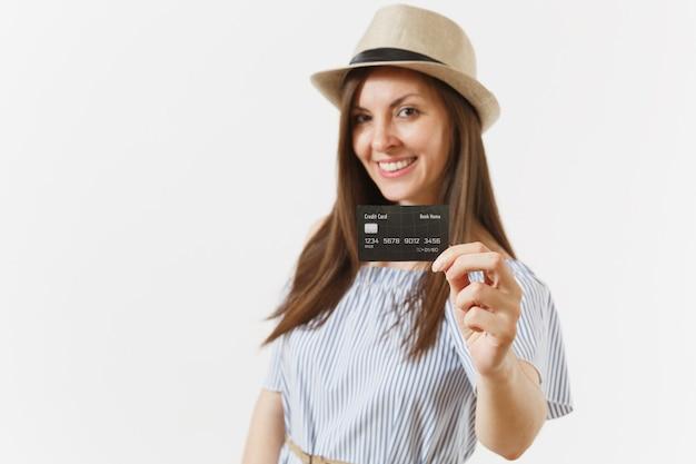 Jeune femme élégante charmante en robe bleue, chapeau aux longs cheveux bruns tenant montrant la carte de crédit de l'appareil photo isolée sur fond blanc. concept bancaire de style de vie des gens. espace publicitaire. espace de copie.