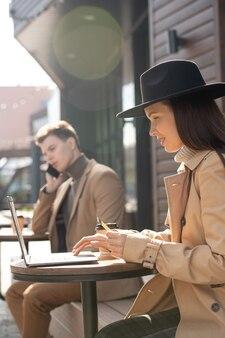 Jeune femme élégante contemporaine tenant une carte de crédit assise près d'une petite table à l'extérieur, faisant des achats en ligne et allant payer l'achat