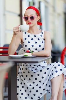 Jeune femme élégante dans un café de rue boit du café. séjour agréable un jour d'été.