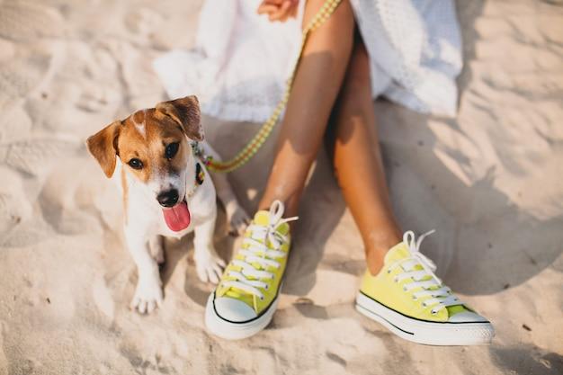 Jeune femme élégante hipster jouant avec sur la plage tropicale