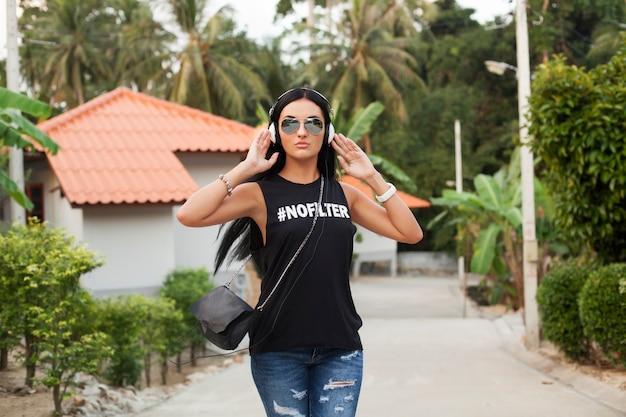 Jeune femme élégante hipster en t-shirt noir, jeans, écouter de la musique au casque, s'amuser, marcher dans la rue, vacances d'été, profiter