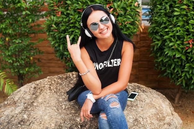 Jeune femme élégante hipster en t-shirt noir, jeans, écouter de la musique au casque, s'amuser, poser, drôle, souriant