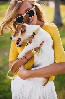 Jeune femme élégante hipster tenant marcher et jouer avec un chien