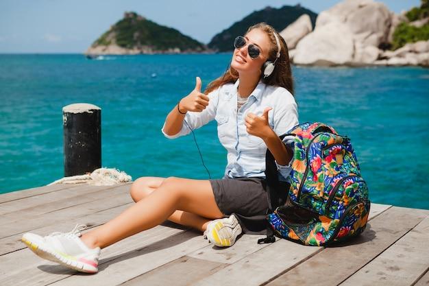 Jeune femme élégante hipster voyageant à travers le monde, assis sur la jetée, lunettes de soleil aviateur, écouteurs, écouter de la musique, vacances, sac à dos, chemise en jean, heureux, lagon de l'île tropicale
