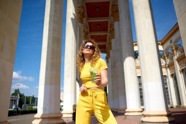 Jeune femme élégante avec une limonade à pied et voir des sites touristiques en voyage