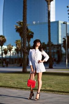 Jeune femme élégante marchant seule, tenue et accessoires élégants à la mode, dame sexy d'âge moyen, couleurs toniques, allées de palmiers.