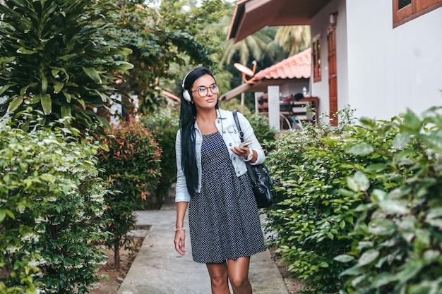 Jeune femme élégante marchant avec smartphone, écoutant de la musique au casque, vacances d'été