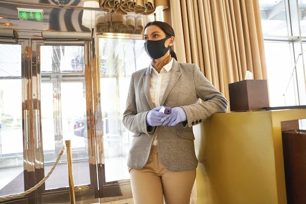 Jeune femme élégante en masque médical et gants en caoutchouc debout à l'entrée de l'hôtel prête à vérifier la température