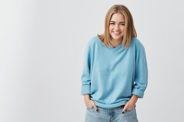 Jeune femme élégante à la mode d'apparence européenne portant un pull bleu et un jean, souriant largement, démontrant ses dents blanches parfaites, tenant ses mains dans les poches. jeunesse et bonheur